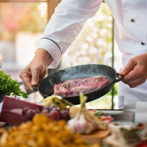 Chef cuisinier qui cuit une viande